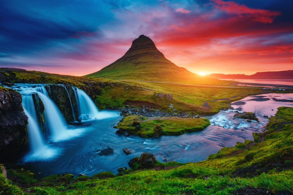 Waterfalls tumble on a green landscape with a rounded mountain head in the background. Colourful sunset skies. National parks of Iceland.