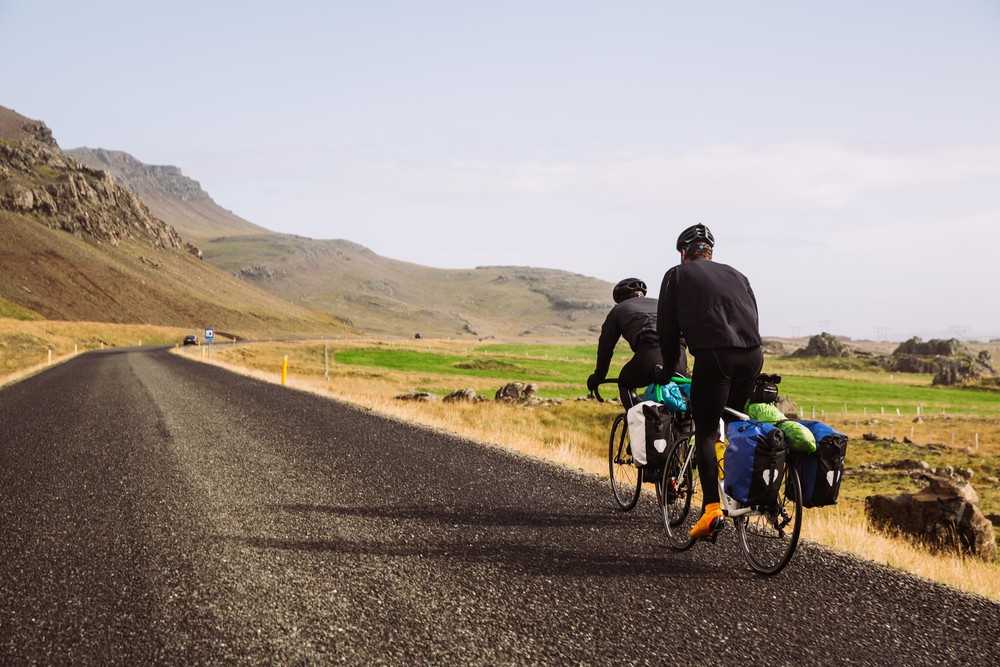 Cycling in Iceland. Two road bikers cycle along a flat road through mountain scenery and blue skies.
