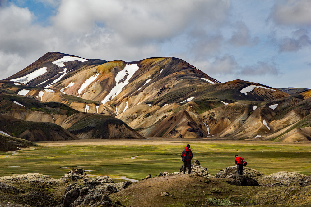 Hikers look out at a view of coloured mountains striped with snow. They stand amidst a green landscape. The Laugavegur Trail is popular for hiking in Iceland