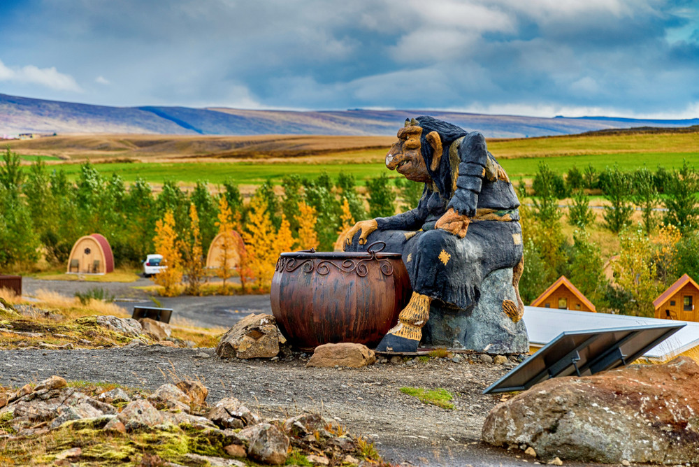 Model of a troll sitting next to a cauldron in Icelandic countryside on a fine day. Trolls in Iceland are everywhere.