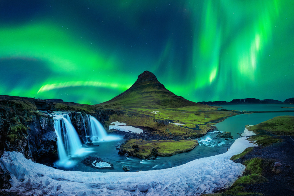 Northern Lights above mountain and waterfall. Iceland in Fall.
