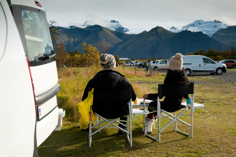 Two people seated on chairs enjoying the view over a pretty campsite to the mountains beyond. How to find the best camper rental in Iceland.