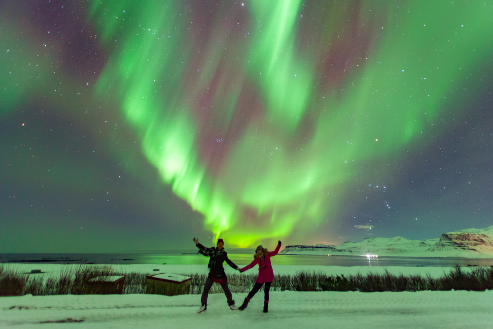 Couple dancing in front of green Northern Lights in winter landscape. Camping Golden Circle, Iceland.