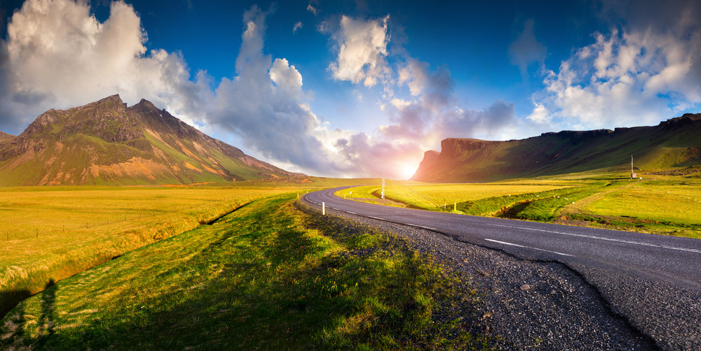 Blue skies and low sun, view of a road winding through a green and mountainous landscape. Driving safely in Iceland.