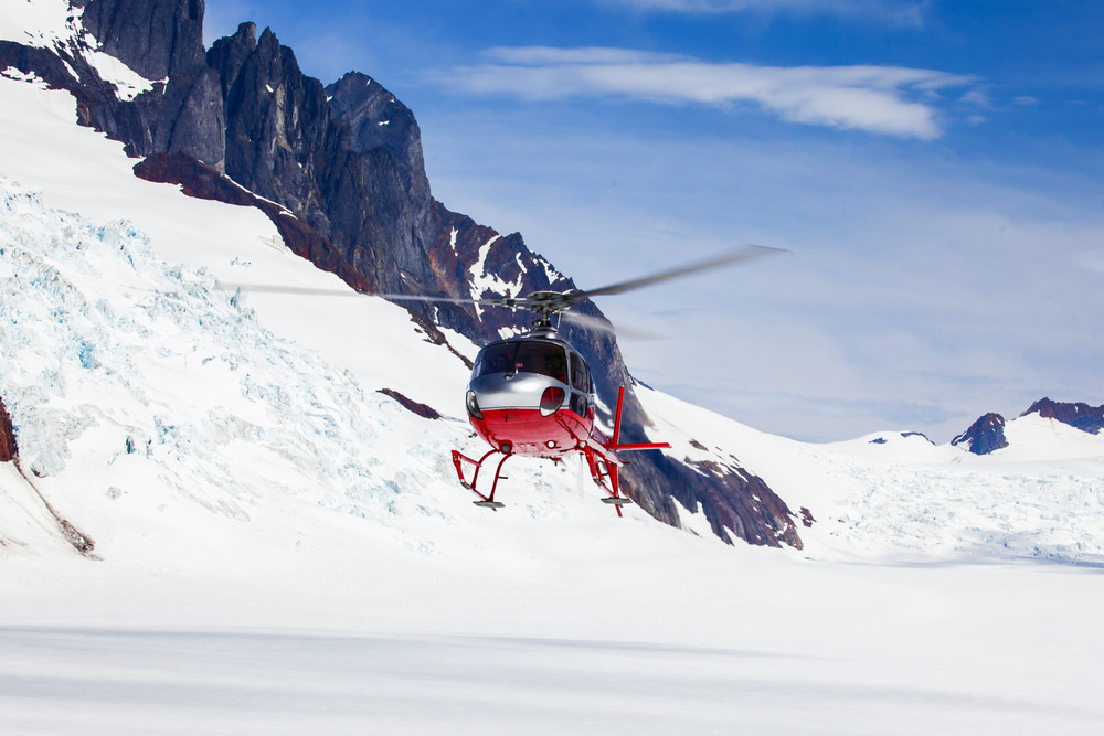 Red helicopter in remote winter landscape. Skiing in Iceland.