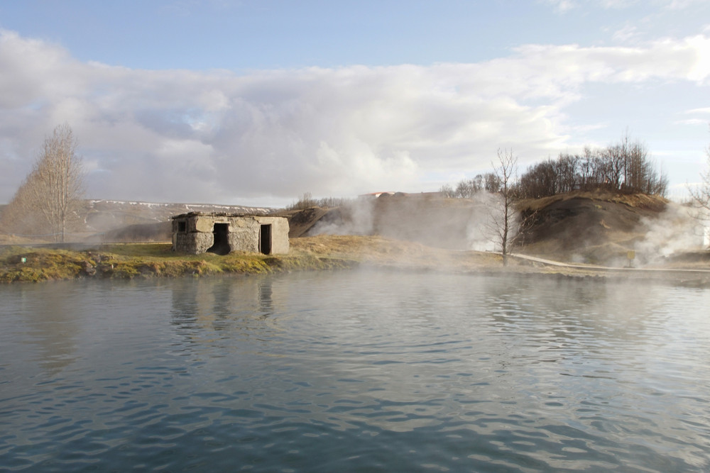 A peaceful lagoon with rising steam and a rustic building in the distance. No people. The Secret Lagoon is one of the loveliest pools and hot springs in Iceland