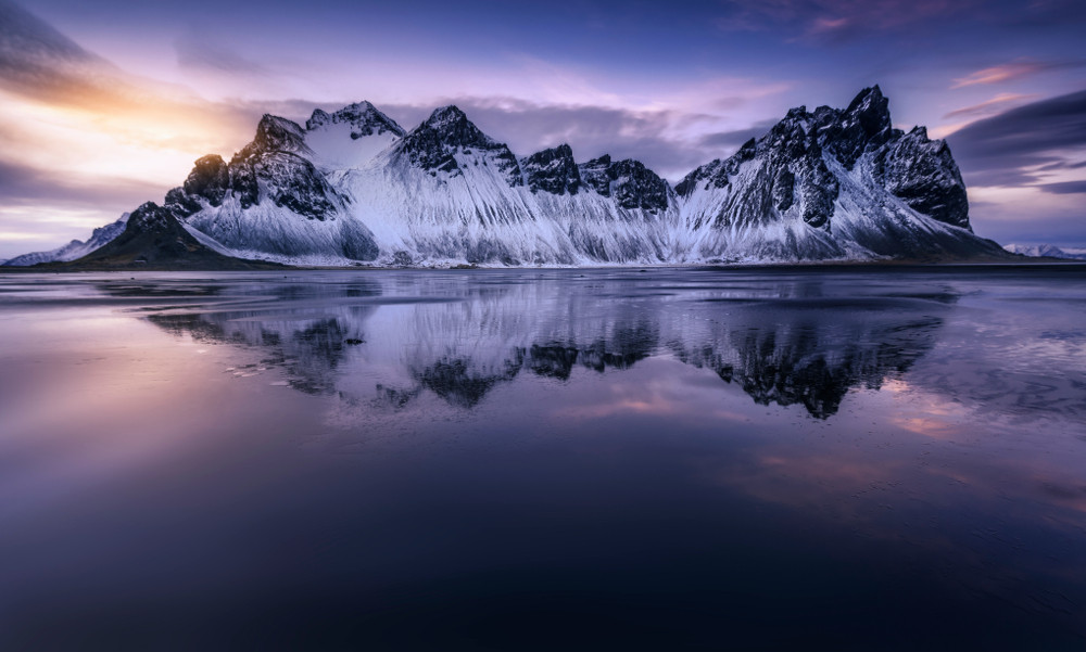 Icy mountains across a calm lake and low purple and orange twilight. Does Iceland get Polar Nights