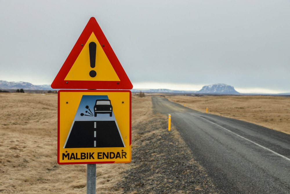 Road transition paved to gravel and a yellow and red warning sign. Grey day and unfenced road running through grassland. Driving on gravel roads in Iceland.