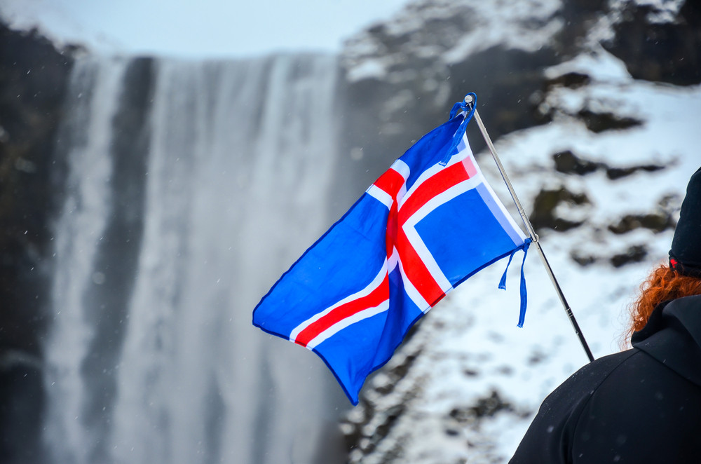 person holding Iceland national flag next to large waterfall