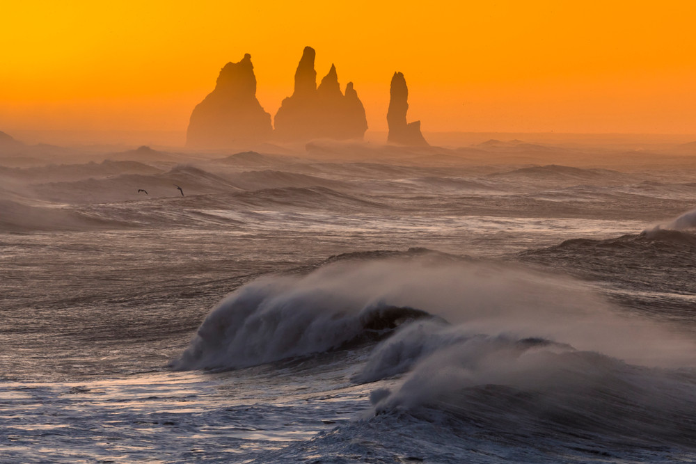 Ocean view to rock pillars and a red sky.  Iceland in October.