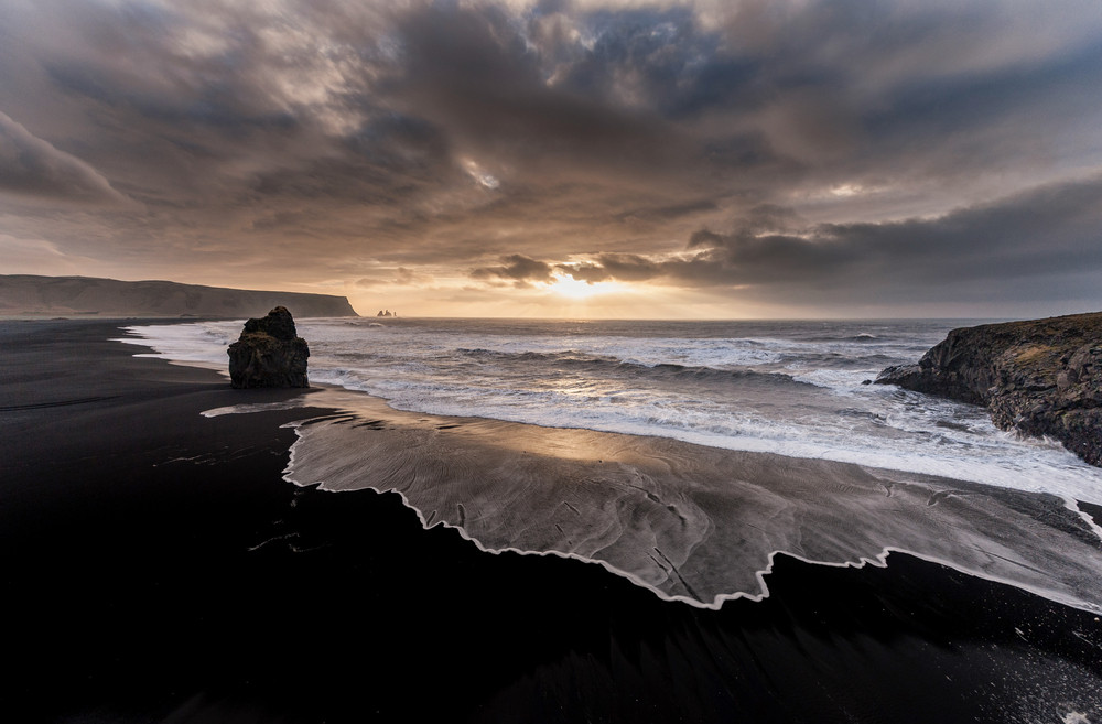 Dark skies and low sun over black sand beach and ocean. Moody Iceland photography.