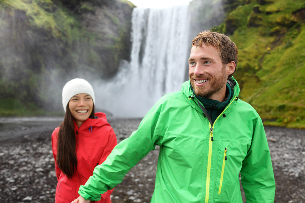 Smiling young couple in rain coats walking away from a waterfall. August in Iceland.