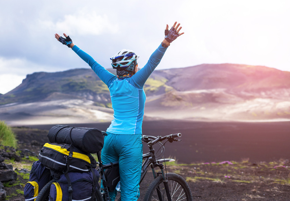Happy person dressed in blue cycling in Iceland. Saddle bags and bike and view over mountains.