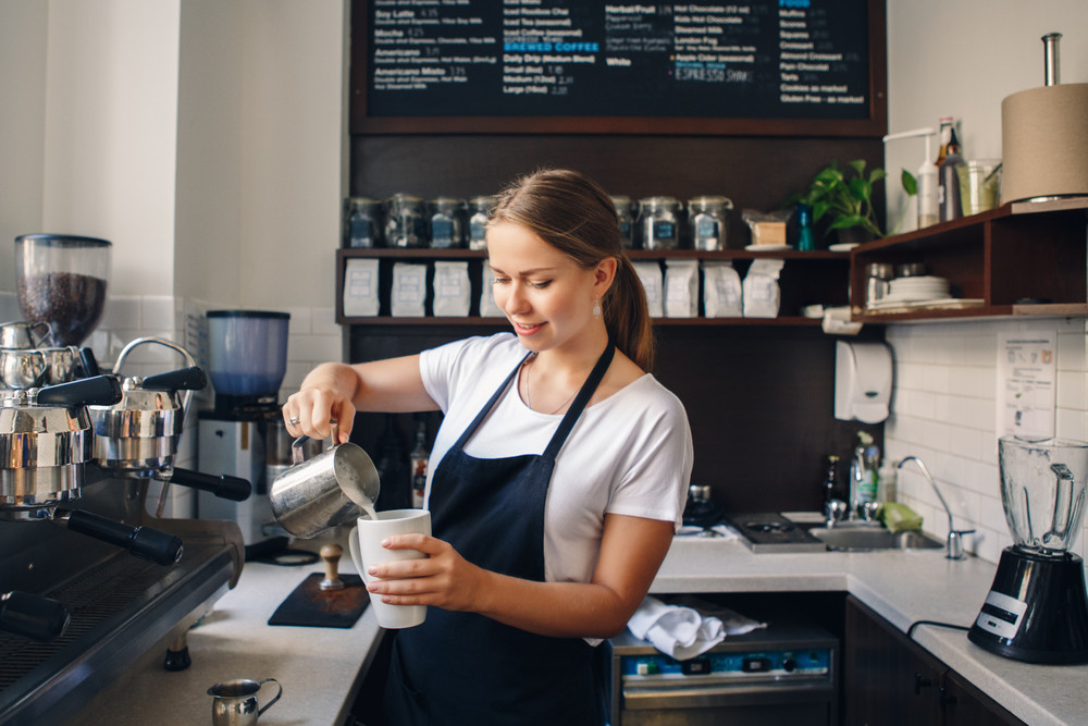 Woman pouring milk into a cup behind a coffee shop counter. Do i need a visa in Iceland?