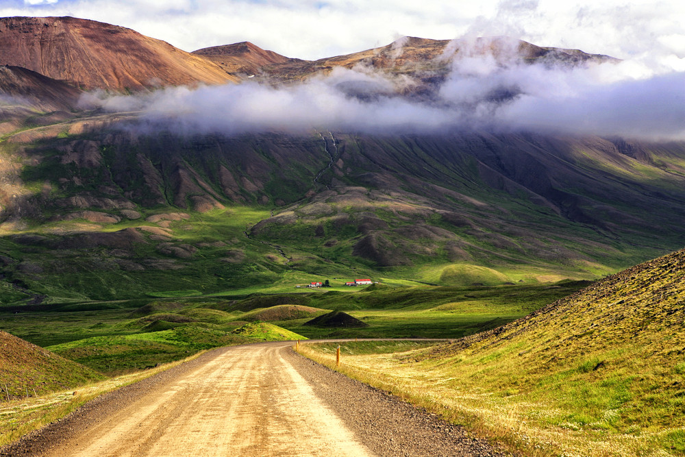 Dramatic landscape view with gravel roads in Iceland. Mountains and low cloud in a green valley.