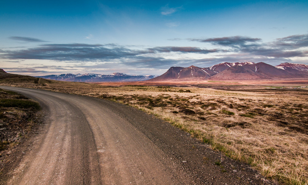 Lonely landscape and muted colours. A gravel road leads off into grassland and mountain scenes. Driving on gravel roads in Iceland.