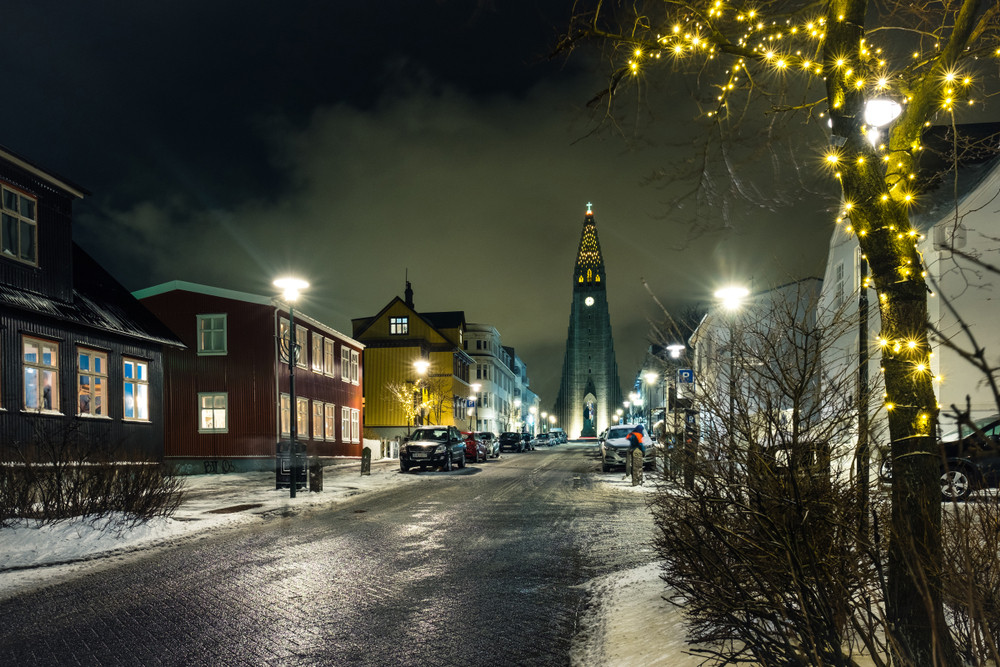 Wintery nighttime street scene with a tall church in the distance and frosty pavements. Reykjavik is the venue for Iceland Airwaves Festival in November.