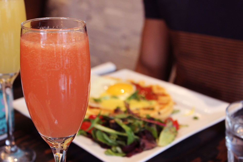 pink mimosa and blurred brunch plate behind. Brunch and breakfast in Reykjavik.