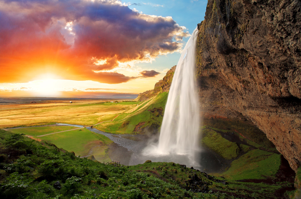 Seljalandsfoss Waterfall flow with sunset and green landscape in Iceland.