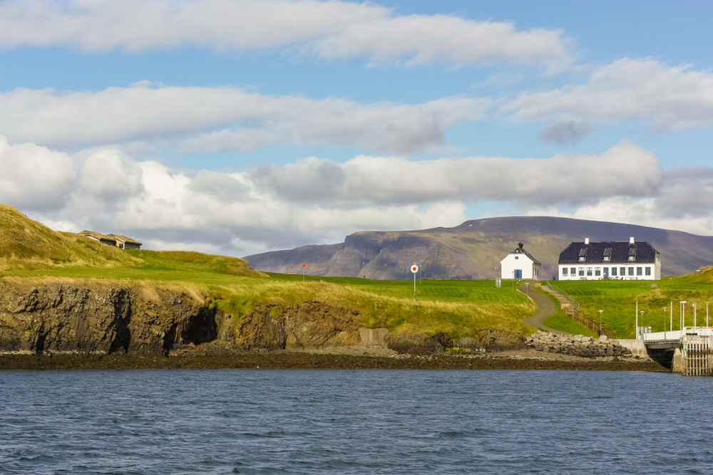 View of an island with one house and green hills.Travel to Videy Island is included on the Reykjavik City Card.