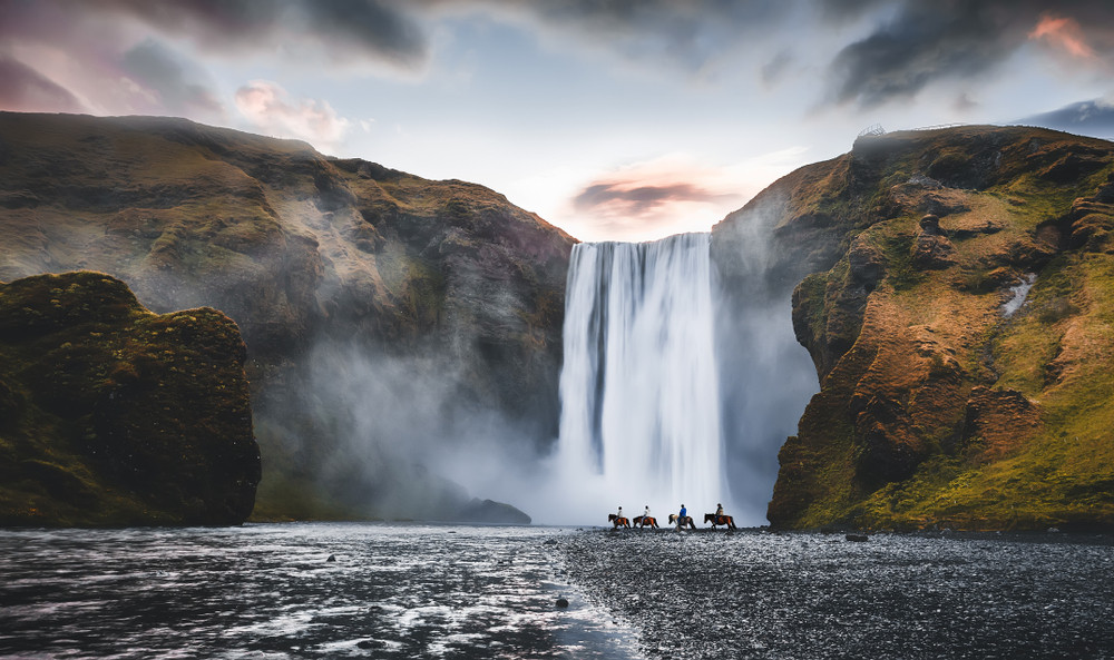 Impressive view of a waterfall with four horses and rider walking past in distance. Iceland photography of moody sky and landscape.
