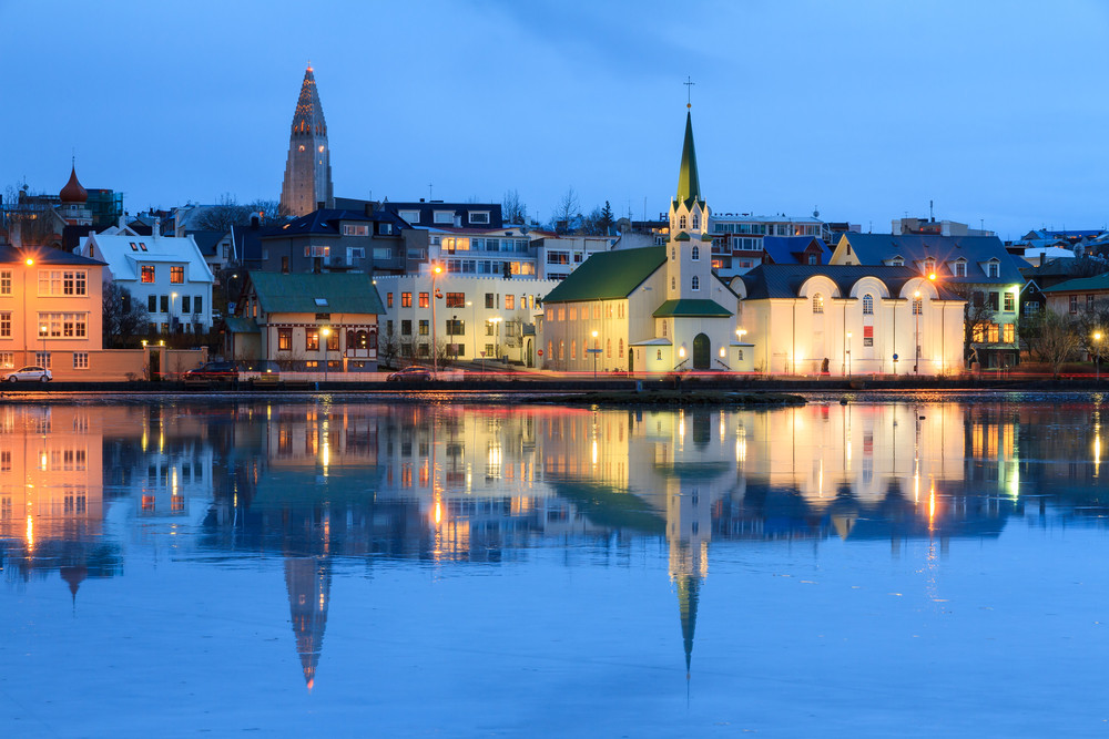 View of waterfront buildings reflected in water at dusk. Reykjavik the capital cities in Iceland.