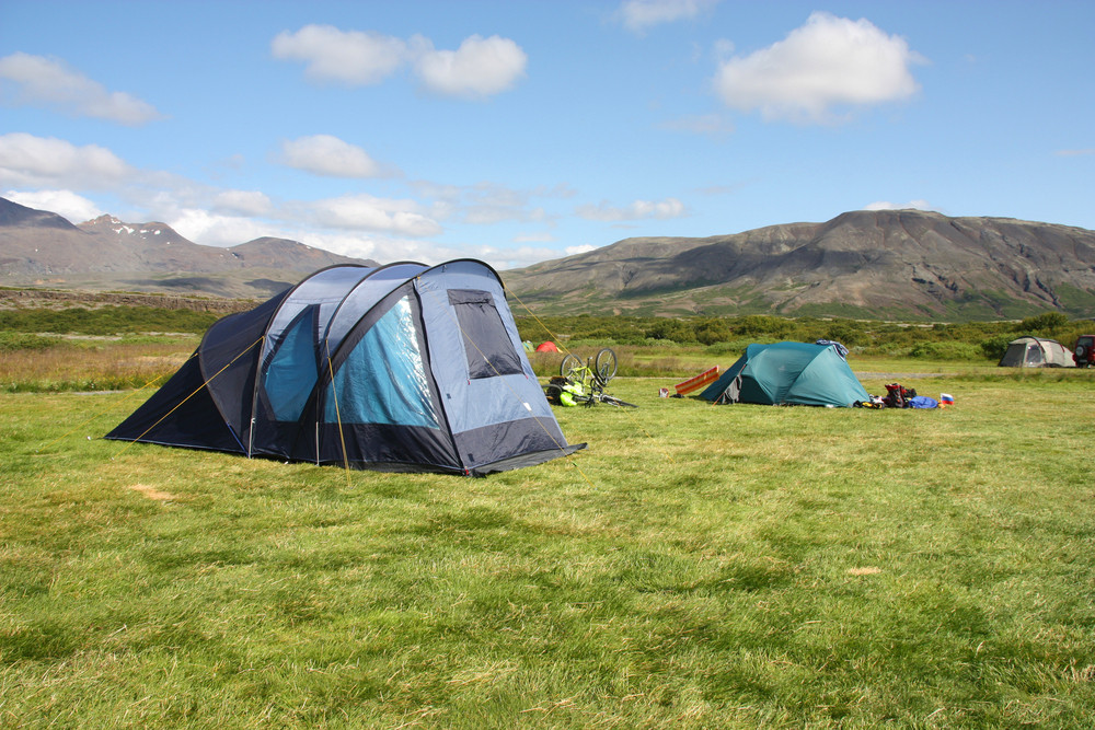 2-3 tents in a flat green field with mountain vires and blue skies. Iceland's Golden Circle.
