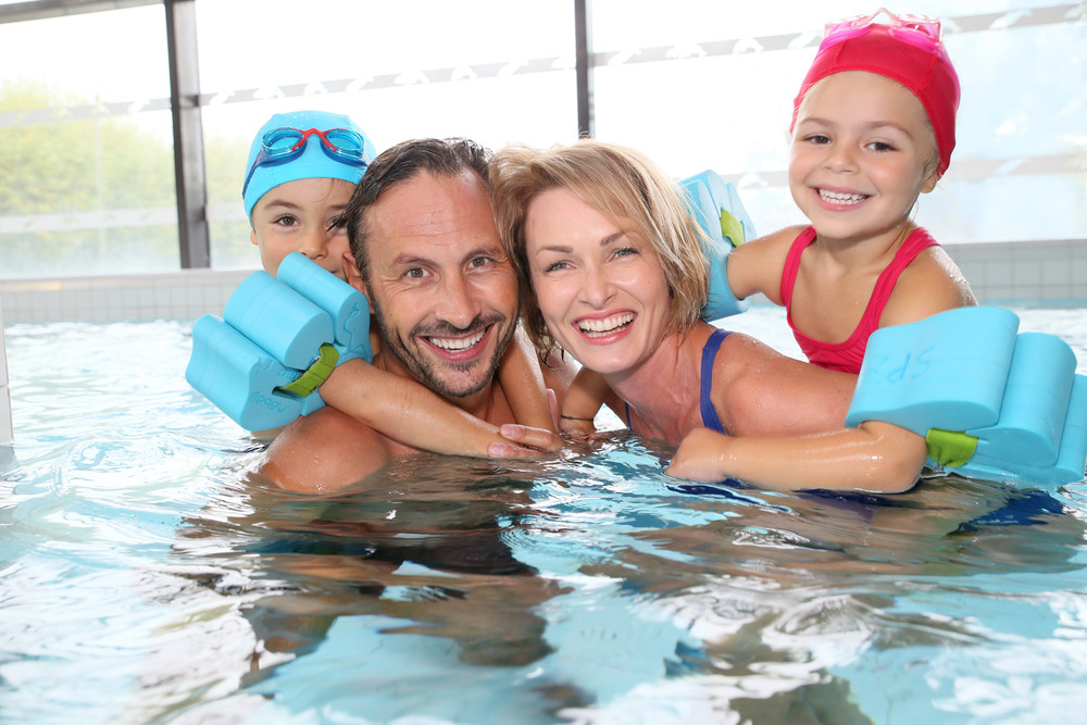 Family in a public pool. Young children wearing blue arm bands and smiling couple. Entry to pools included on the Reykjavik City Card