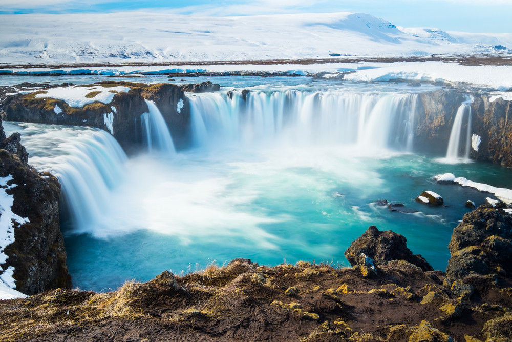 Wide horseshoe of waterfalls in Iceland with a snowy landscape behind.