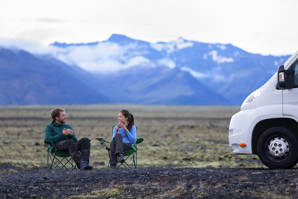 Young couple relax in camping seats near camper van in mountain scenery. Camping near Jokursarlon Glacier Lagoon