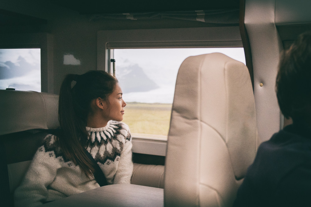 Young woman smiling out window of motorhome. Advantages of driving a motorhome in Iceland.