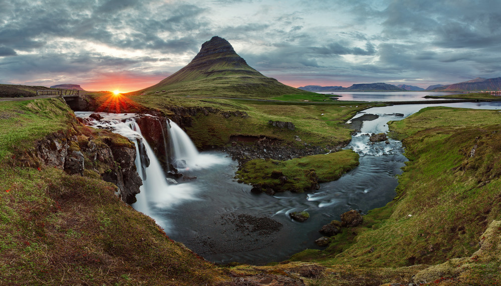 Rounded green mountain and waterfall under moody sky and low sun. Photography locations in Iceland.