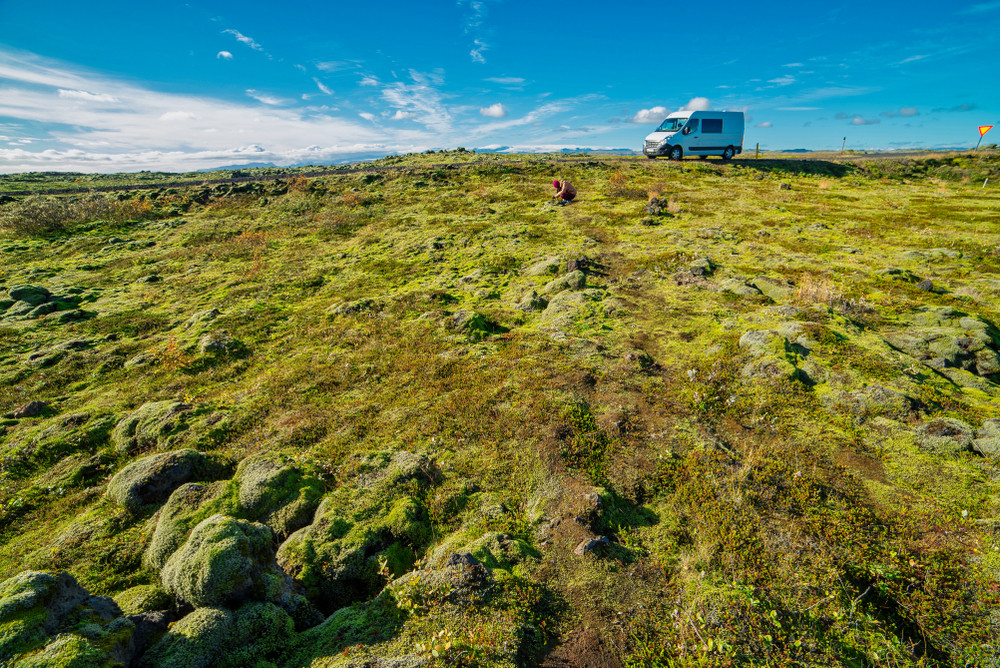 View of motorhome across moss-covered rocks. Advantages of driving a motorhome in Iceland.