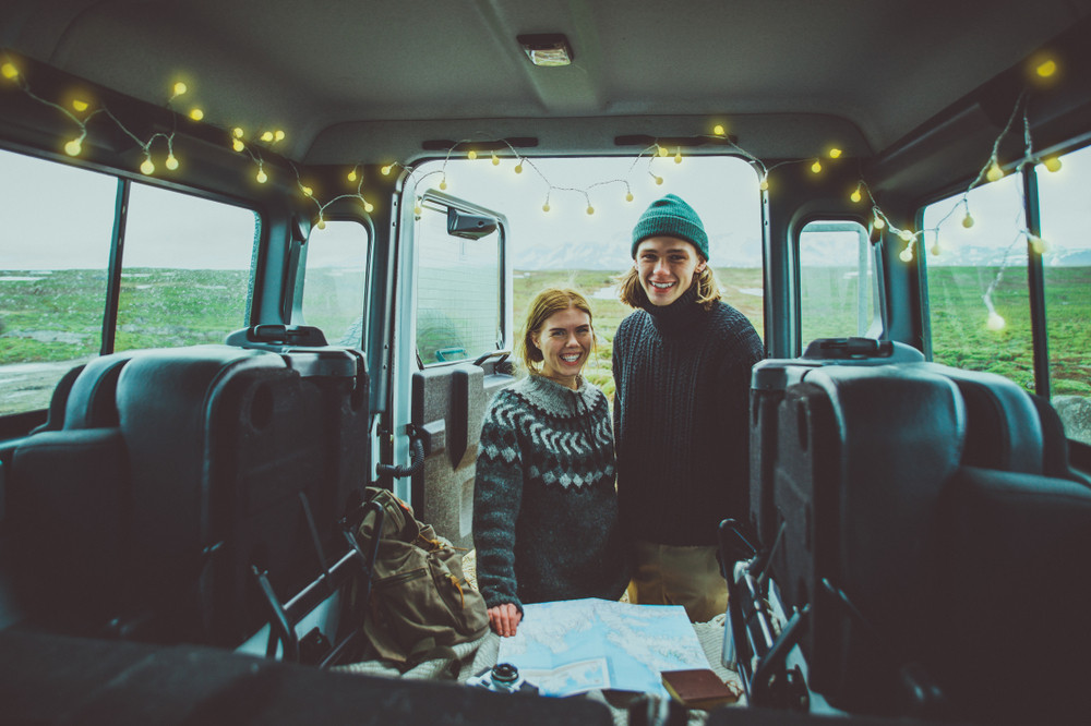 Smiling young couple stand at back doors of a cute camper with fairy lights. View from inside. Self-drive road trips in Iceland.