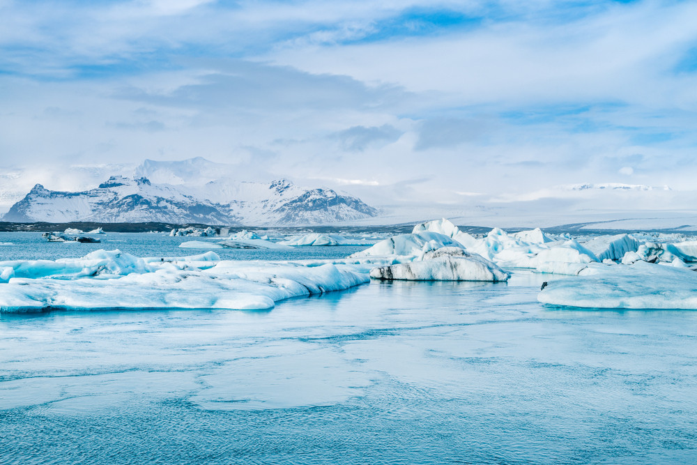 Blue and white, a lake of floating icebergs with snowy mountains and heavy sky behind. Jokursarlon Glacier Lagoon.