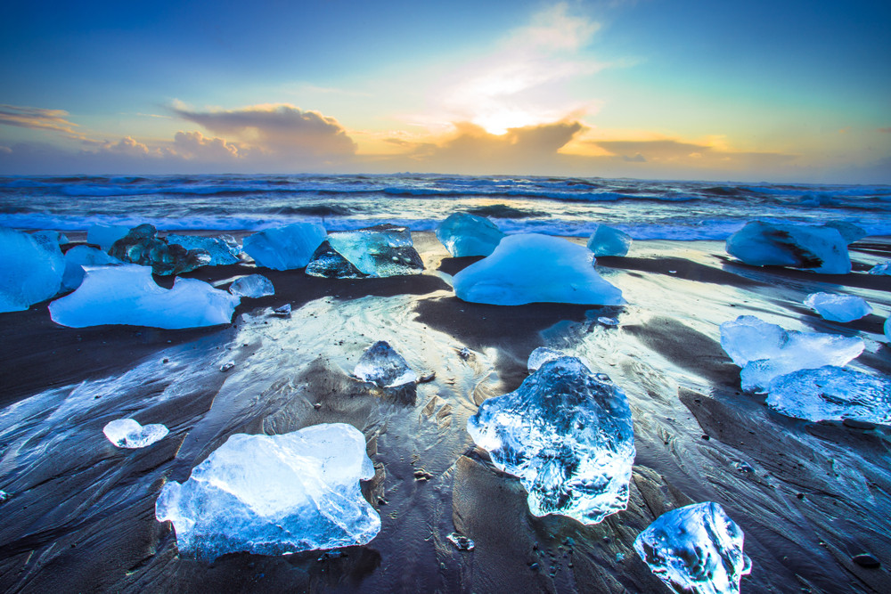 Large pieces of glowing blue ice on a beach at sunset. Diamond Beach one of the top Iceland Beaches.