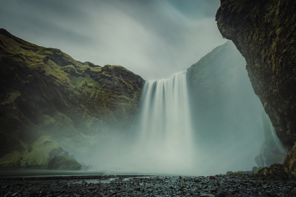 Large waterfall plunging down a cliff with moody skies and black rocky terrain. The Skogafoss Waterfall is a Season 8 Game of Thrones filming locations in Iceland