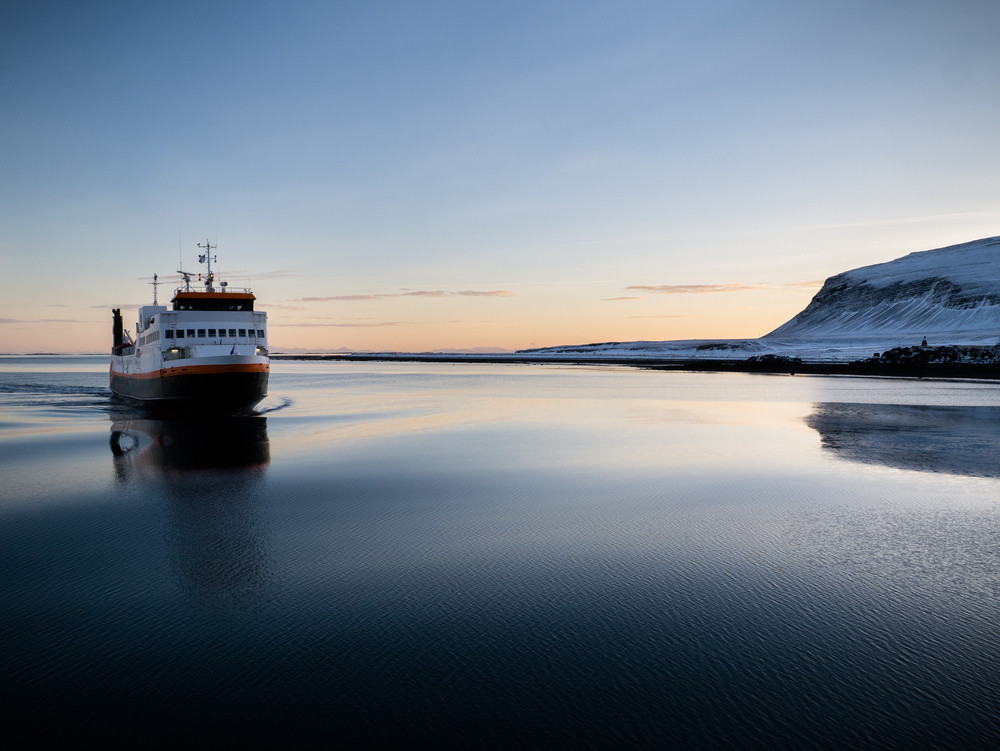 Ferry on a flat sea at dusk. Ferries in Iceland.
