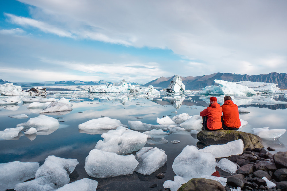 Couple dressed in red sit and look out across a glacier lagoon. Romantic places in Iceland.