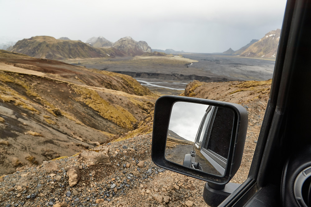View in 4x4 side mirror along high mountain road in volcanic landscape. Do I need a 4 x 4 in Iceland?