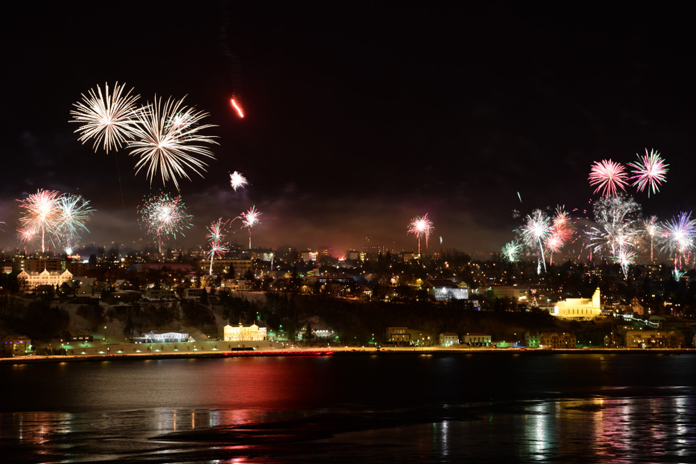 Fireworks over a city. View from the sea. August in Iceland.