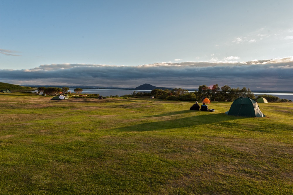 A few tents on expansive green area next to lake. Lake Mývatn is one of the nicest campsites in Iceland.