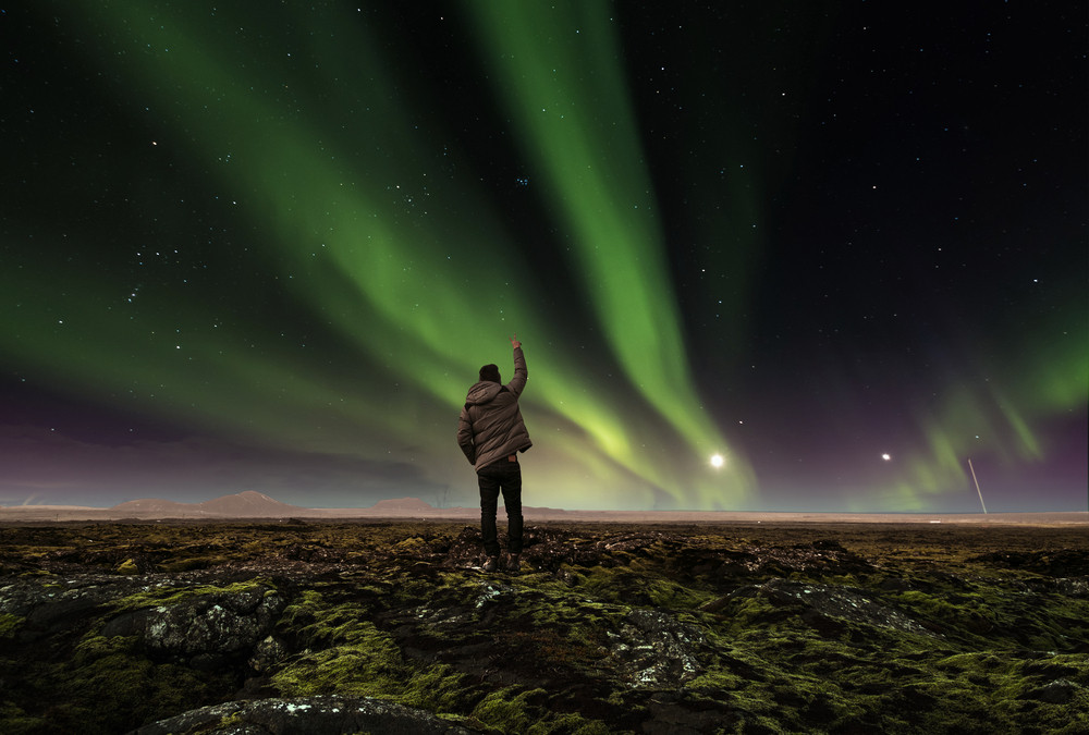 Starry night, mossy landscape. Man in winter gear stands with peace sign in the air and the green of the northern lights glows above him. How to see the Northern Lights.