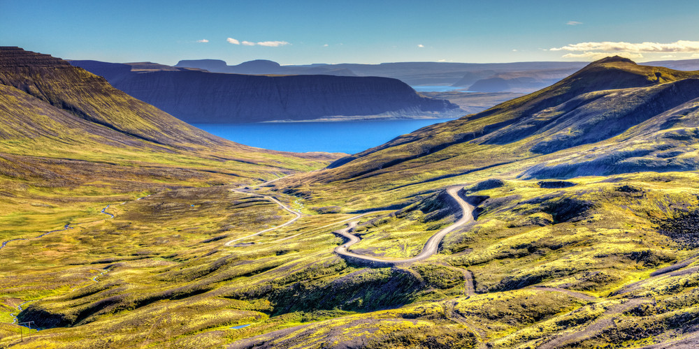Exploring the Westfjords, Iceland. Empty road winding through countryside to the distant sea.