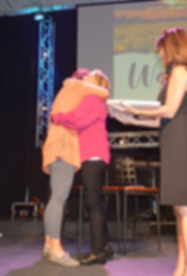 Laura Busse hugging an attendee of the 3 O'Clock Wake Up Call conference.