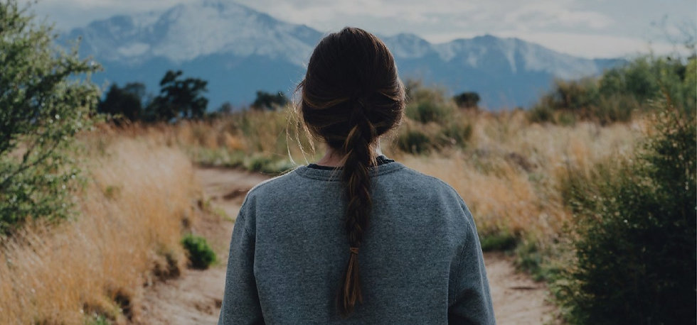 Woman standing on a hiking trail looking at the mountains ahead.