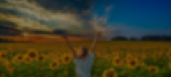 Woman standing in a field of sunflowers giving thanks to God.