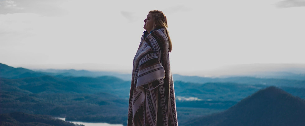 Woman wrapped in a blanket on a mountain giving thanks to God.