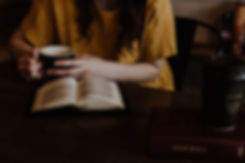 Woman sitting at a table and drinking coffee while doing a bible study.