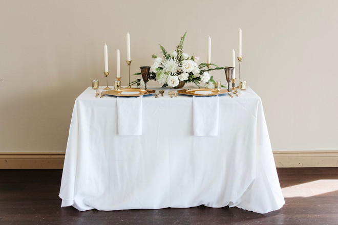 Small long table set for 2, with white and gold colour palette.